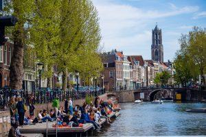 Mensen genieten van het weer aan de gracht in Utrecht